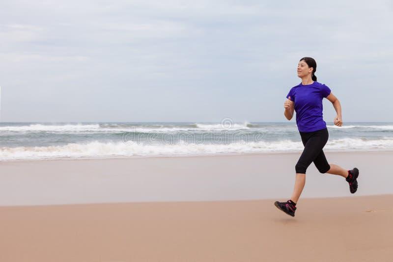 Spring för kvinnlig idrottsman nen på stranden fotografering för bildbyråer