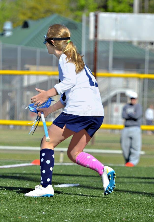 Spring för ung flickalacrossespelare royaltyfri bild