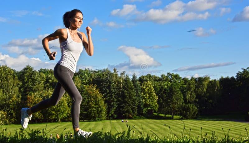 Spring för ung kvinna i parkera under sportutbildning royaltyfria foton
