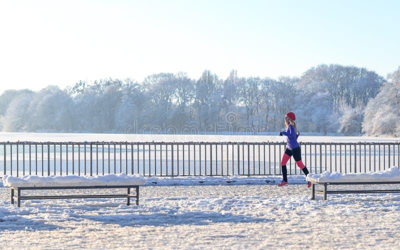 Spring för ung kvinna i vintersnö arkivfoto