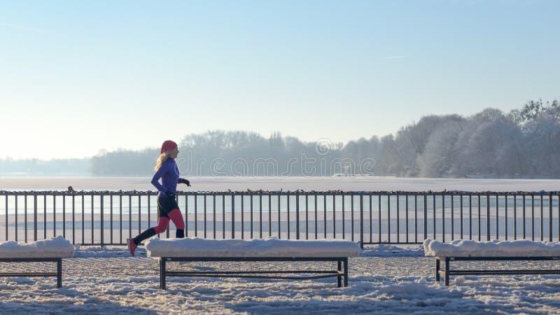 Spring för ung kvinna i vintersnö arkivbilder