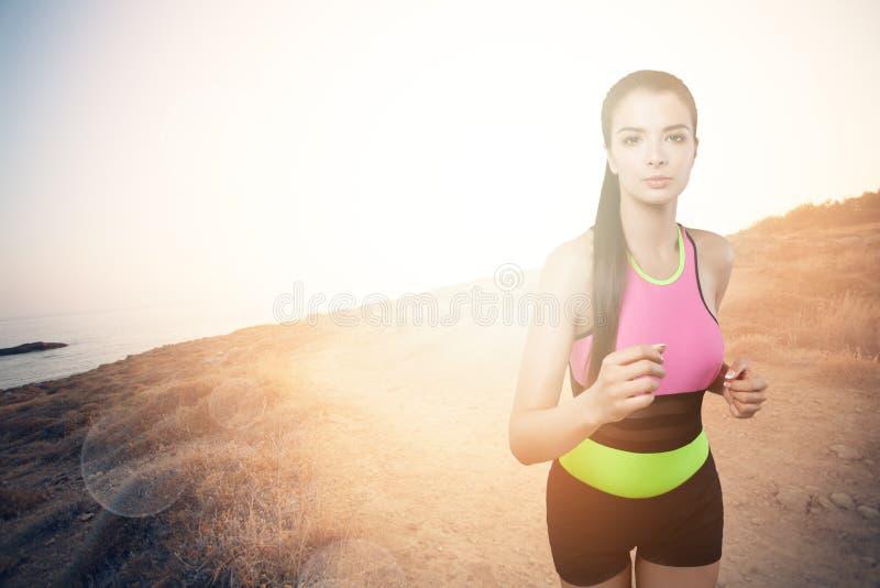 Spring för ung kvinna på bergslinga Jogga för flickalöpare royaltyfri foto