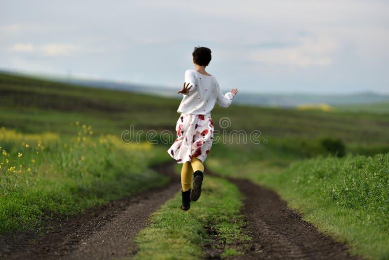 Spring för ung kvinna på en bygdväg arkivfoto