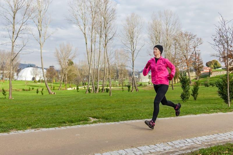 Spring för ung kvinna på en kall vinterdag arkivfoto