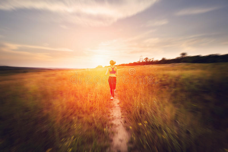 Spring för ung kvinna på en lantlig väg på solnedgången royaltyfria bilder