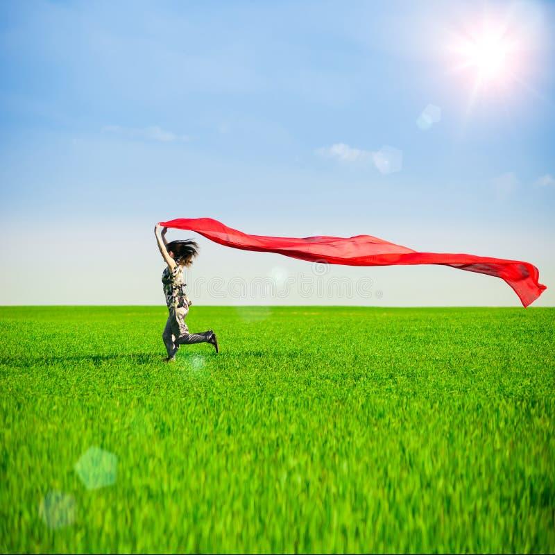 Spring för ung kvinna på en lantlig väg på solnedgången i sommarfält Bakgrund för livsstilsportfrihet royaltyfria foton