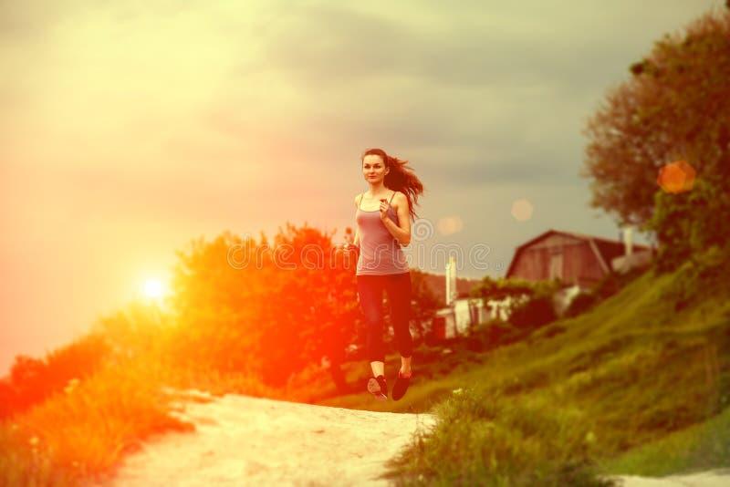 Spring för ung kvinna på en lantlig väg under solnedgång royaltyfria foton