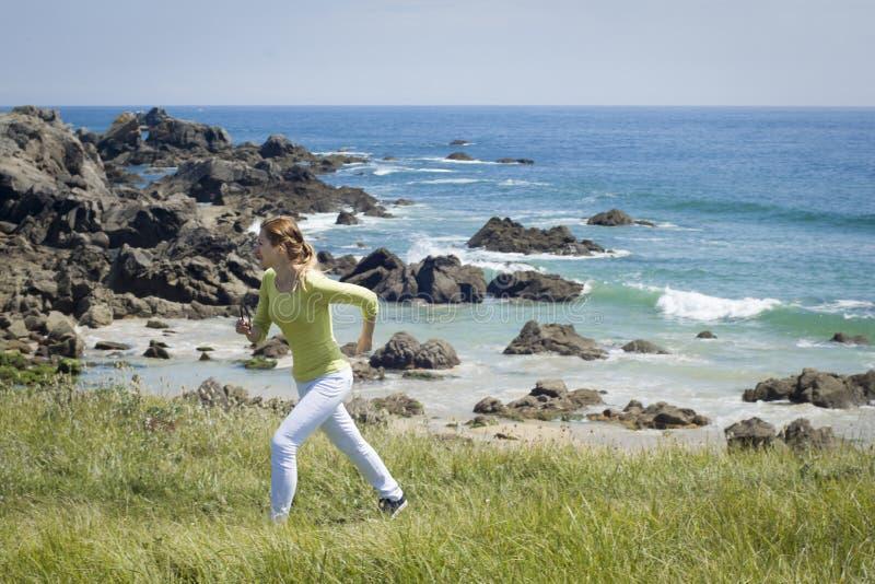 Spring för ung kvinna på en sjösida fotografering för bildbyråer