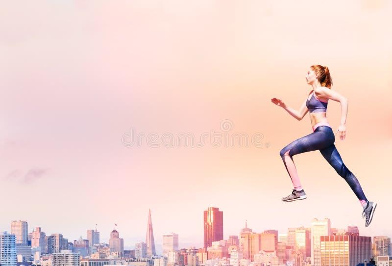 Spring för ung kvinna på solnedgång royaltyfri bild
