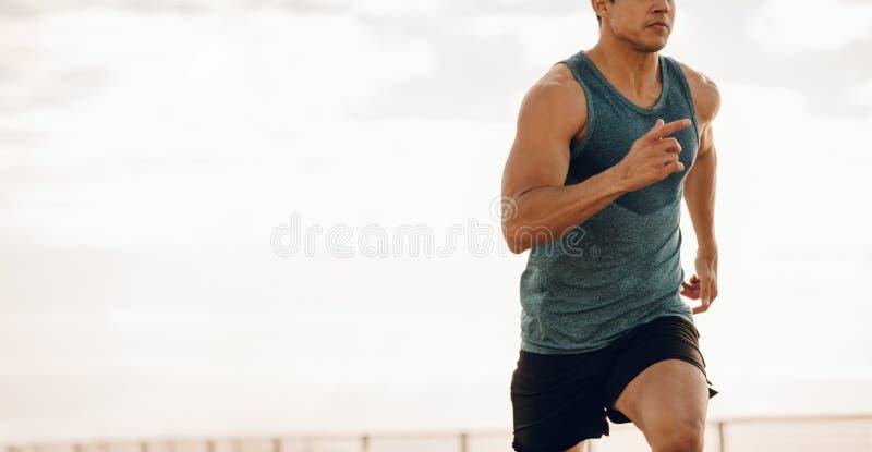 Spring för ung man längs en sjösidapromenad royaltyfri bild