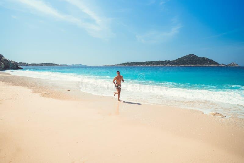 Spring för ung man på havsstranden Manlig löpare som joggar under t royaltyfria bilder