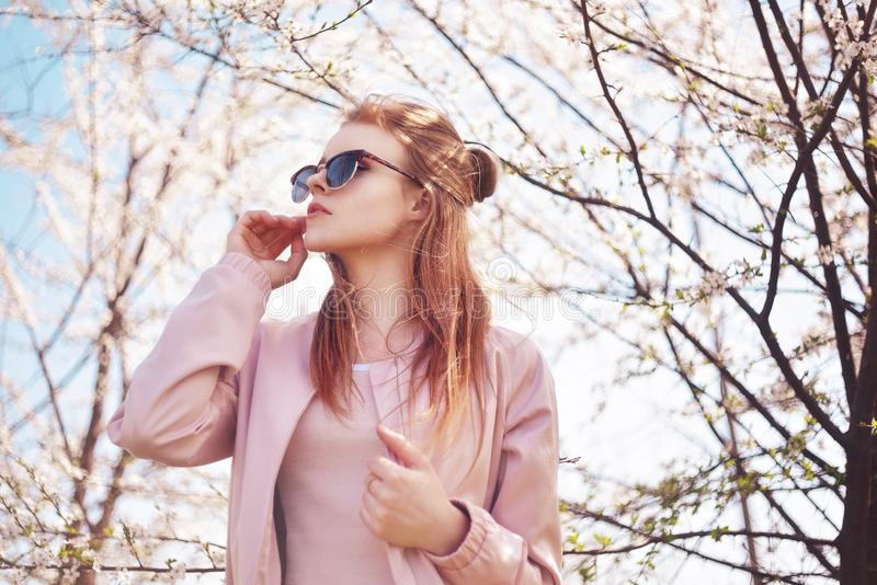 Spring fashion girl outdoors portrait in blooming trees. Beauty Romantic woman in flowers in sunglasses. Sensual Lady. royalty free stock images