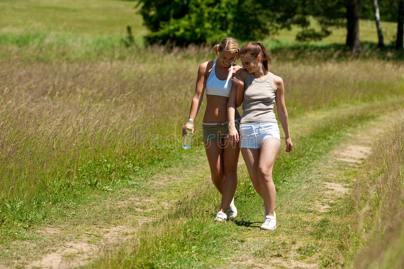Spring - Female couple walking in nature. Summer - Female couple walking in nature on a sunny day stock image