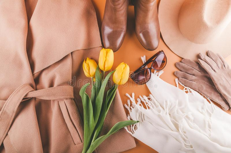 Spring female outfit with yellow tulips. Set of clothes, shoes and accessories on orange background stock photos