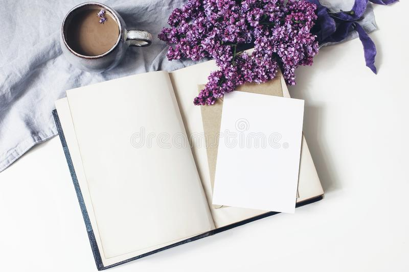 Spring feminine scene, floral composition. Bunch of purple and white lilac flowers, old book, cup of coffee and linen stock image