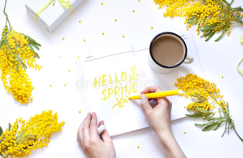 Spring flat lay with yellow flowers, notepad . Woman`s hand are writing in notebook. royalty free stock photos
