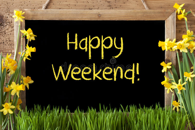 Spring Flower Narcissus, Chalkboard, Text Happy Weekend. Blackboard With English Text Happy Weekend. Spring Flowers Nacissus Or Daffodil With Grass. Rustic Aged royalty free stock image
