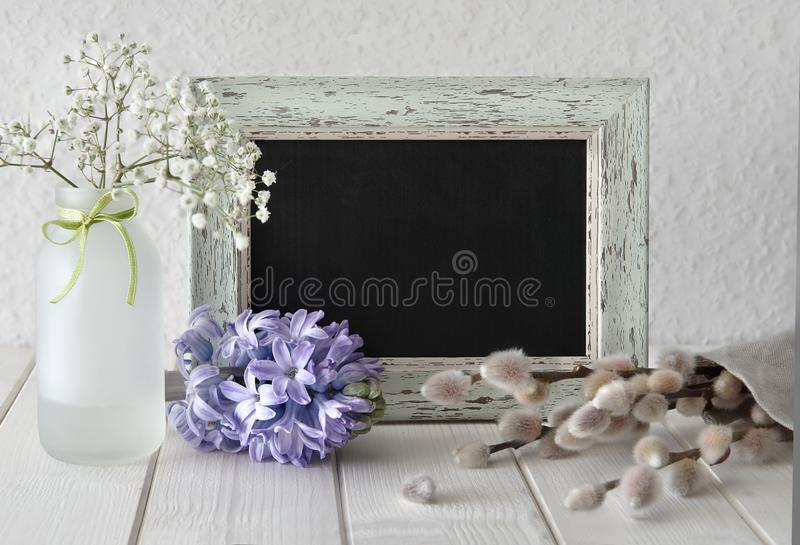 Spring flowers around a blackboard in rustic frame, text space royalty free stock photo