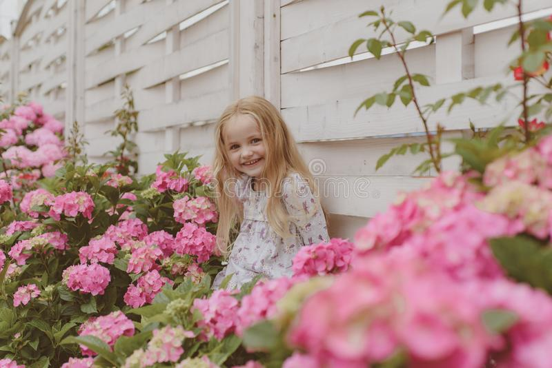 Spring flowers. Childhood. Little girl at blooming flower. Summer. Mothers or womens day. Childrens day. Small baby girl royalty free stock photos