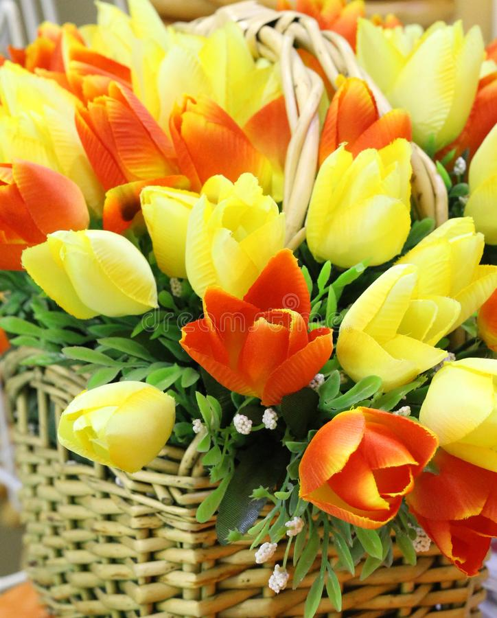 Spring flowers in the foreground. A bouquet of artificial tulips stands in a wicker basket royalty free stock photo