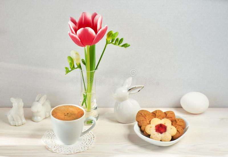 Spring flowers in glass vase, Easter bunnies, espresso and cookies shaped as leaves and flowers stock images