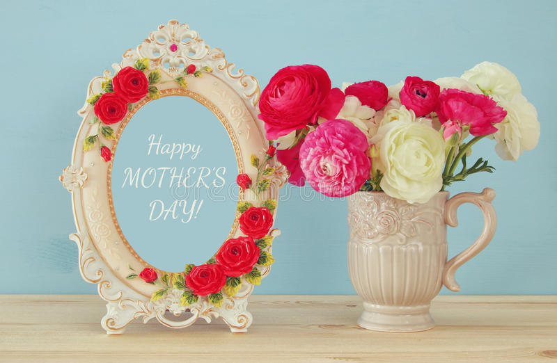 Spring flowers next to photo frame. Mothers day concept. Image of beautiful bouquet of spring flowers next to vintage photo frame. Mothers day concept royalty free stock image