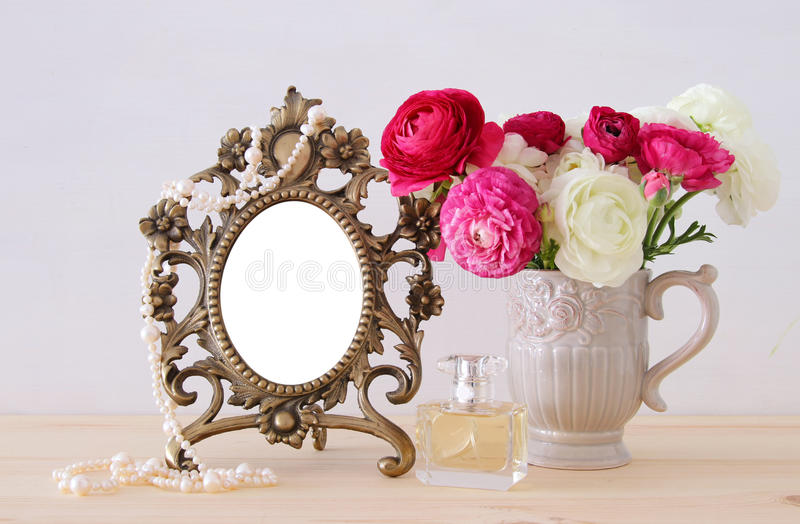 Spring flowers, perfume bottle and pearls next to blank vintage photo frame. Image of beautiful bouquet of spring flowers, perfume bottle and pearls next to stock photos