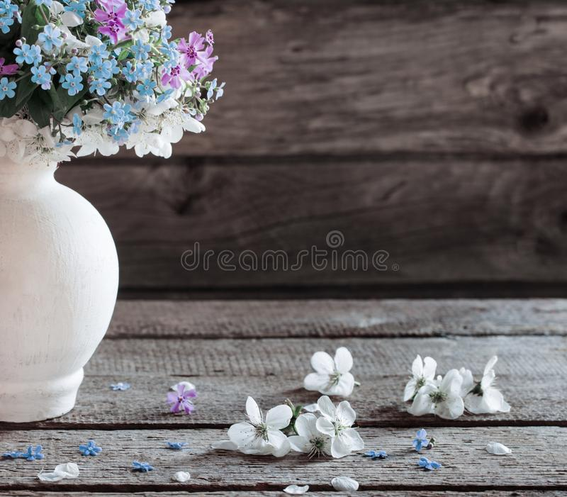 Spring flowers in vase on dark wooden background royalty free stock photography