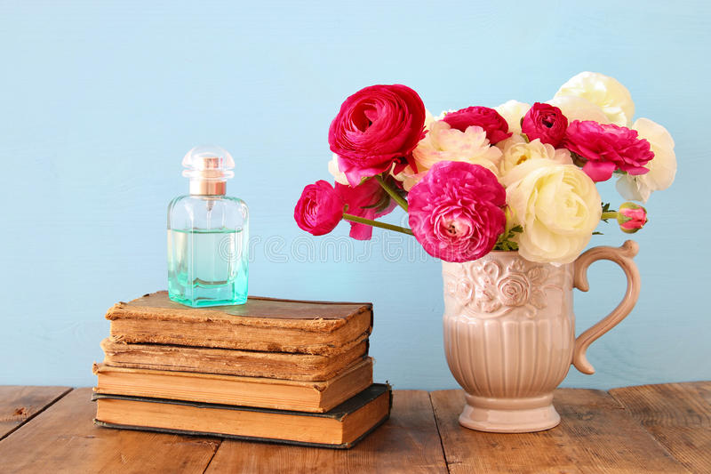 Spring Flowers In The Vase Next To Old Books And Perfume Bottle