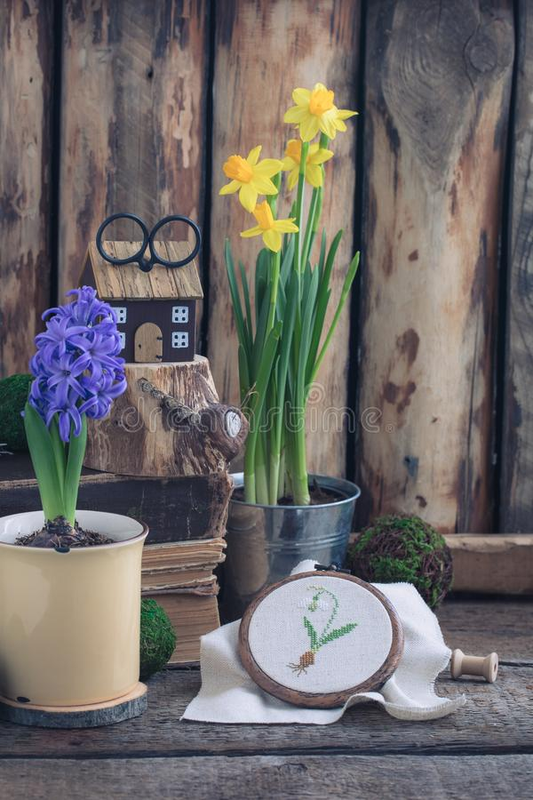 Spring flowers yellow narcissus and blue hyacinth with cross stitched snowdrop on the wooden background. stock images