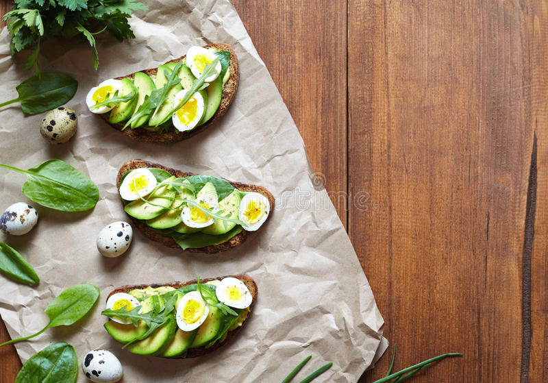Spring food. A whole grain bread toast sandwich with avocado, spinach, guacamole and quail eggs on parchment. royalty free stock photo