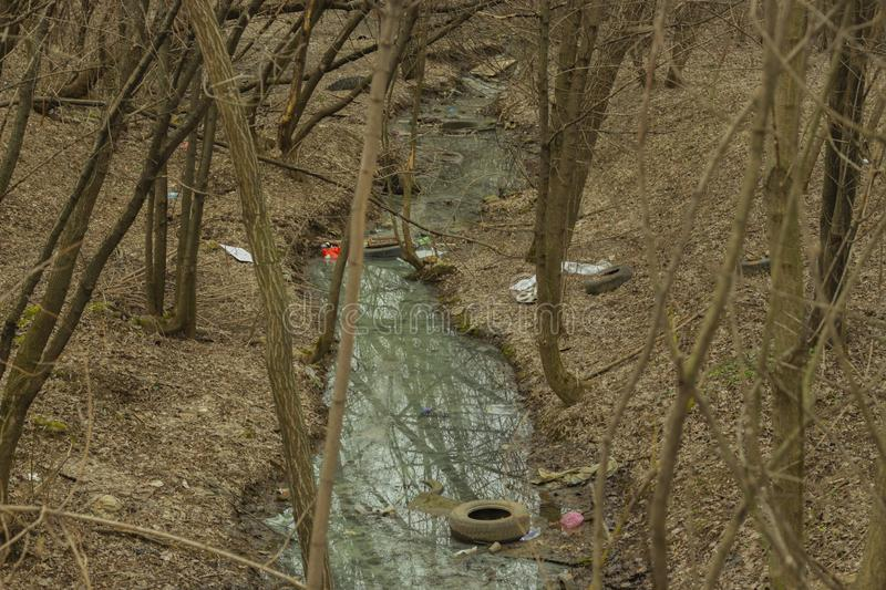 Spring forest stream river garbage waste plastic tire glass bottles. Problems of ecology, pollution of the planet royalty free stock images