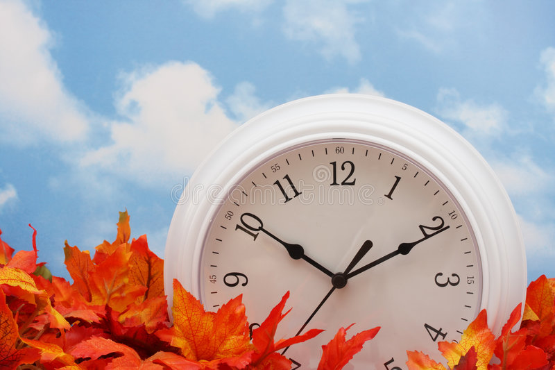 Spring Forward, Fall Back. White clock on fall leaves, sky background royalty free stock photo