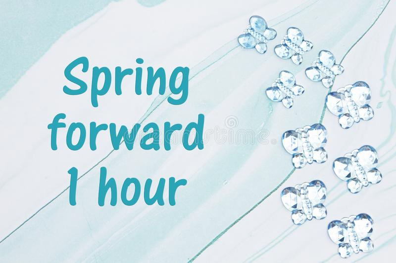 Spring forward 1 hour message with blue glass butterflies on blue watercolor paper royalty free illustration