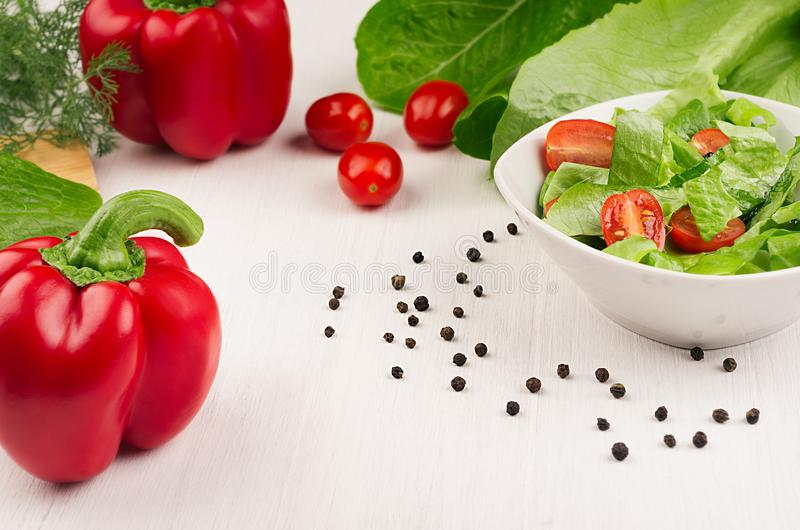 Spring fresh salad of green spinach, cherry tomato slices, red paprika in white bowl on white wood background, closeup, copy space royalty free stock images