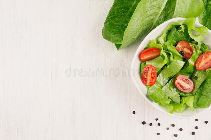 Spring fresh salad of green spinach and cherry tomato slices on white wood background, top view, copy space. royalty free stock photography