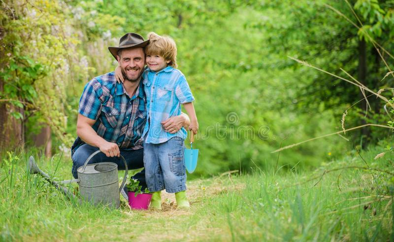 Spring garden. Dad teaching little son care plants. Little helper in garden. Planting flowers. Growing plants. Fresh. Seedlings. Take care of plants. Boy and stock photography