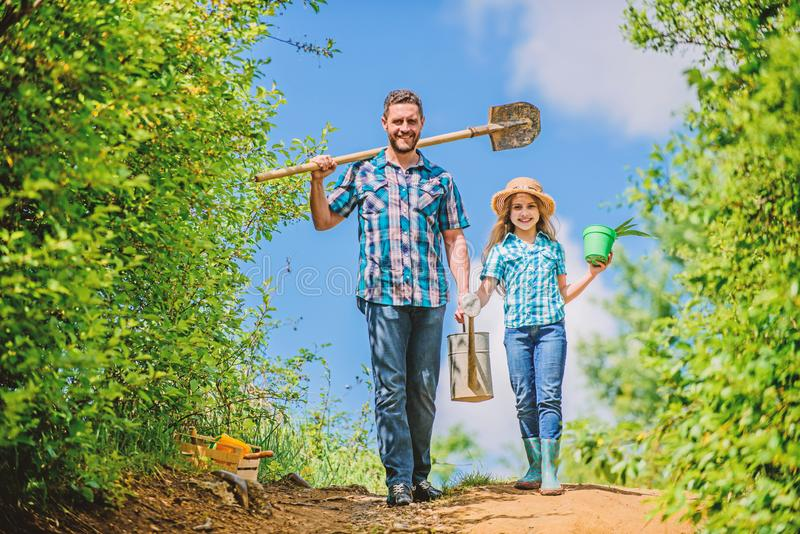 Spring gardening checklist. Father and daughter with shovel and watering can. It is time to plant prepare beds and care royalty free stock photography
