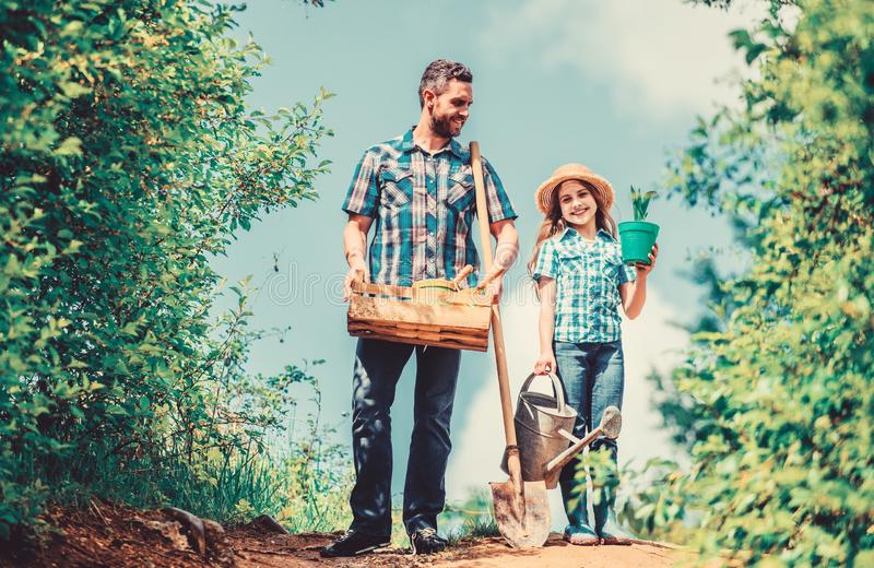 Spring gardening. Spring gardening checklist. Father and daughter with shovel and watering can. It is time to plant royalty free stock photography