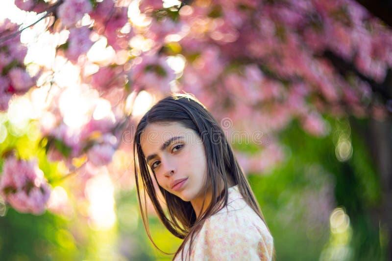Spring girl face. Close up portrait of tender woman at sakura flowers background. Hanami celebration in sakura blooming royalty free stock images