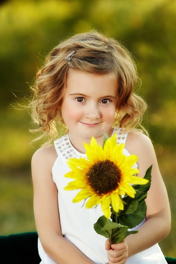 Spring girl. Outdoor portrait of a cute little Caucasian girl with happy smiling facial expression holding a big sunflower in her hands stock photography