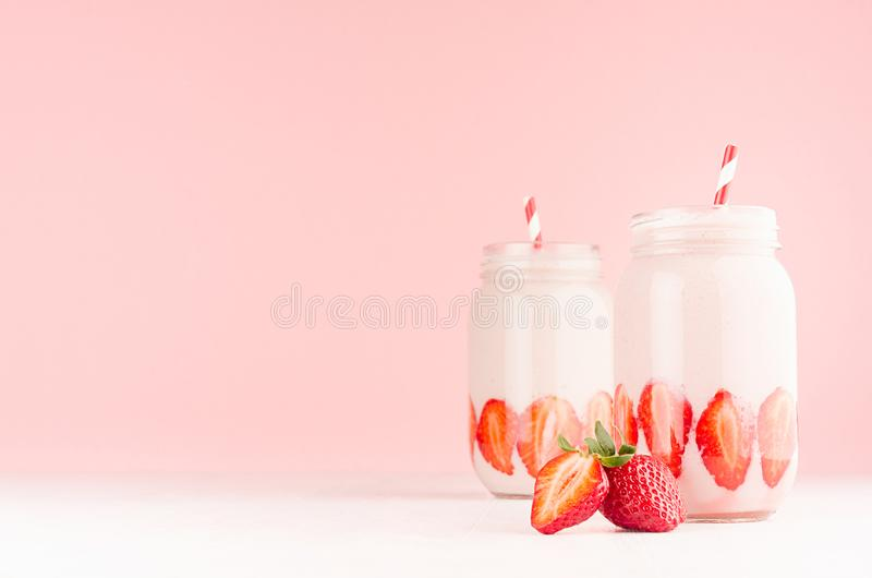 Spring healthy milk beverages with cut ripe strawberry, red striped straws on gentle pastel pink background, white wood table. Spring healthy milk beverages royalty free stock photo