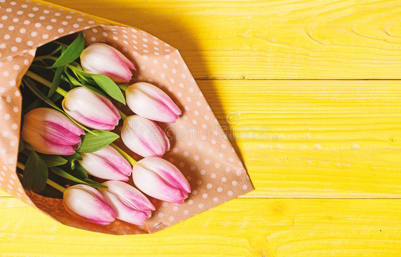 Spring is here. Happy birthday. Bouquet fresh pink tulips on yellow table background top view. Spring holiday greetings. Spring flowers for mothers day. Spring stock photography