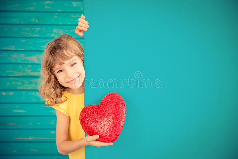 Spring holiday. Father`s day concept. Beautiful child with big red heart hiding behind banner blank. Spring family holiday concept. Father`s day stock photo