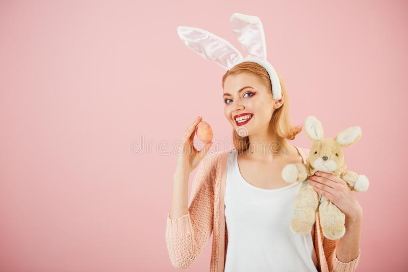 Spring holiday. Girl with hare toy. Happy easter. Woman in rabbit bunny ears. Egg hunt. Easter eggs as traditional food. Happy woman in bunny ears with toy stock photos