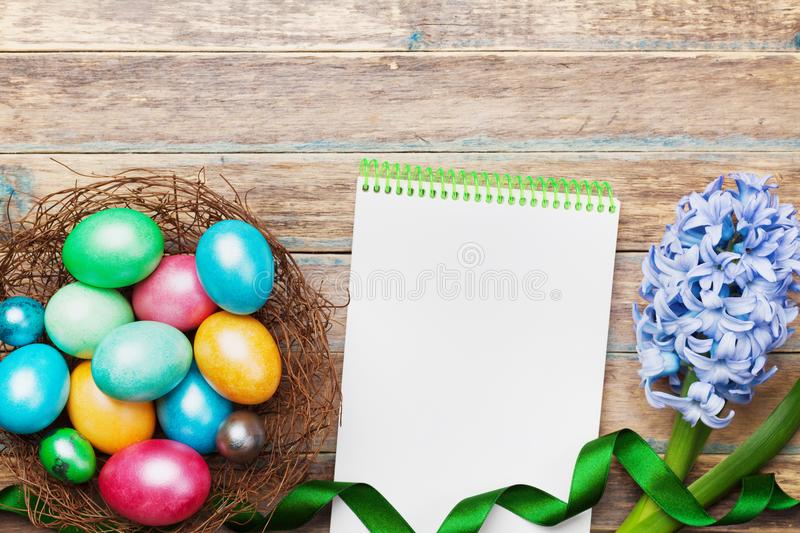 Spring holiday greeting card on Easter with empty notebook for recipe, nest with colorful eggs and flowers on rustic wooden table. stock photos