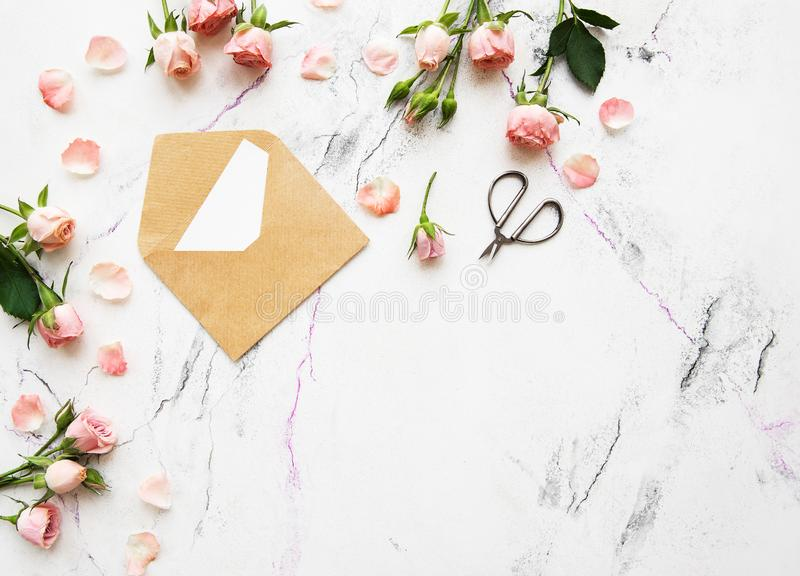 Spring holiday theme. Roses and letter on a white marble background stock photos