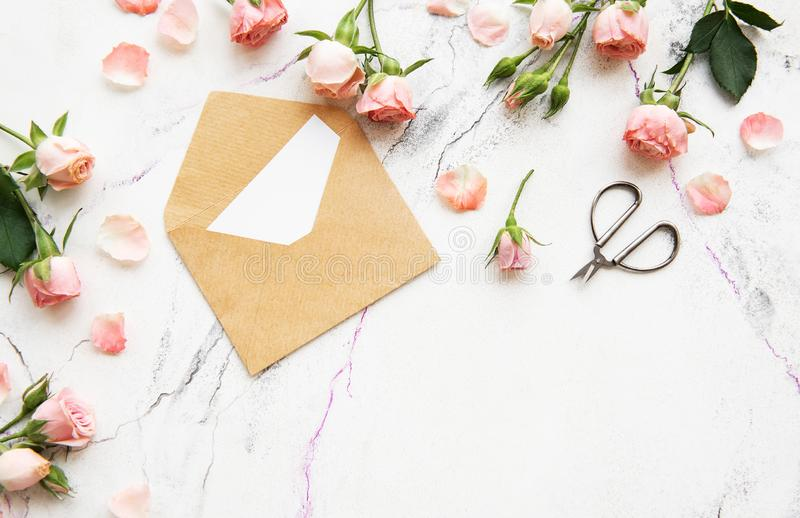 Spring holiday theme. Roses and letter on a white marble background stock photo