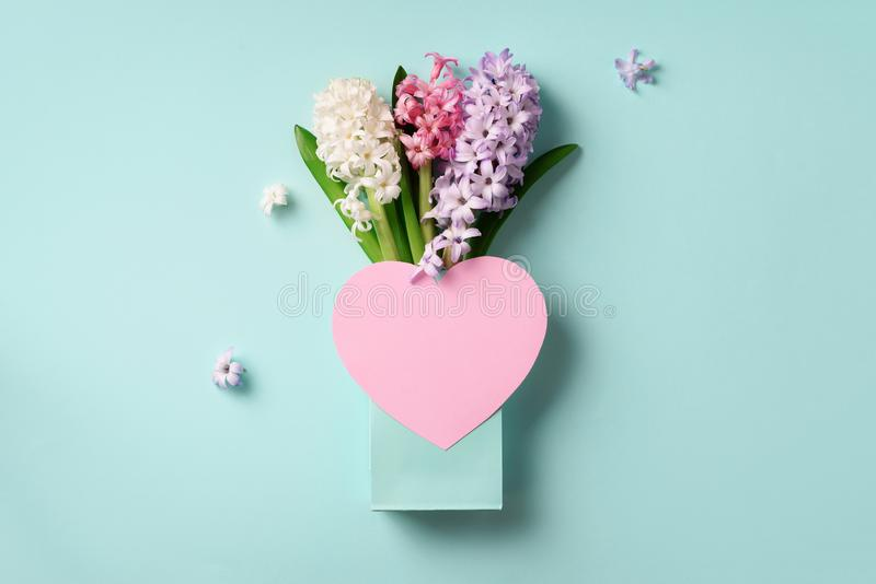 Spring hyacinth flowers in shopping bag, pink paper heart on blue punchy pastel background. Banner with copy space. Spring, summer royalty free stock photos