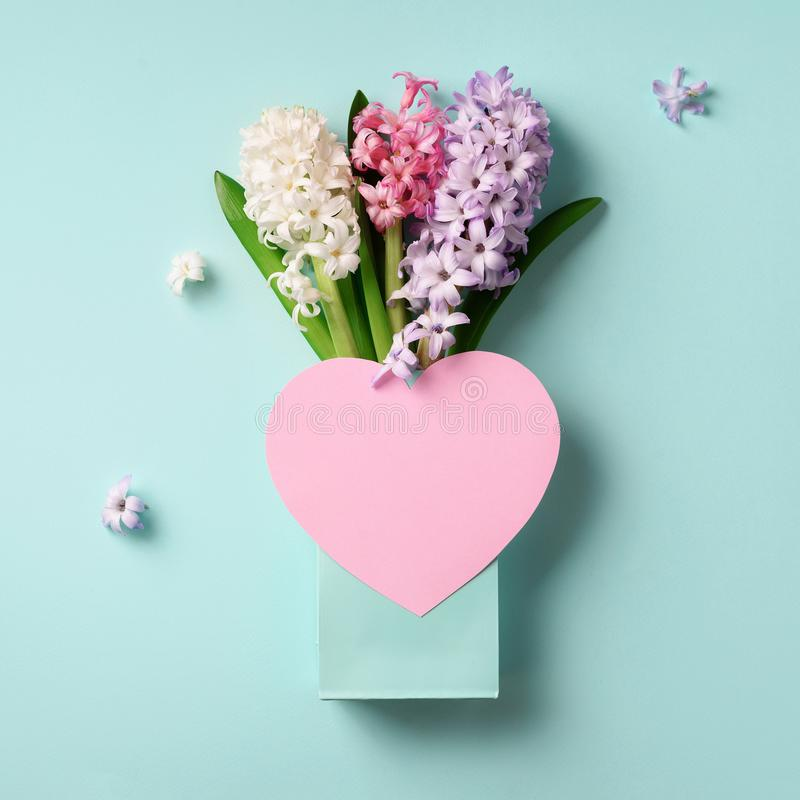 Spring hyacinth flowers in shopping bag, pink paper heart on blue punchy pastel background. Square crop. Spring, summer or garden royalty free stock images